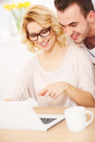 Happy couple using laptop at home Stock Photography