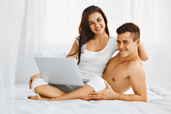 Happy couple using laptop at home Stock Images