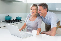 Happy couple using laptop in kitchen Stock Photo
