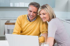 Happy couple using laptop in kitchen Stock Photography