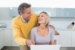 Happy couple using laptop in kitchen Royalty Free Stock Photo