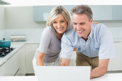 Happy couple using laptop in kitchen Royalty Free Stock Photos