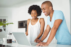Happy couple using laptop in the kitchen Stock Photos