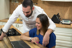 Happy couple using laptop in the kitchen. Stock Images