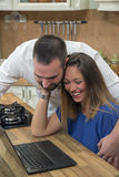 Happy couple using laptop in the kitchen. Royalty Free Stock Images