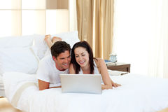 Happy couple using a laptop lying on their bed Stock Images