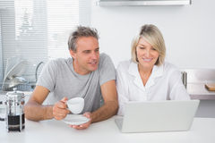 Happy couple using laptop in the morning Stock Image