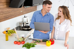 Happy couple using laptop and preparing vegetarian dishes Royalty Free Stock Photo