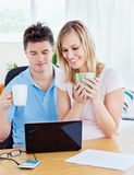 Happy couple using a laptop sitting together Royalty Free Stock Image