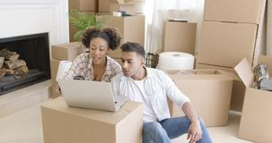 Happy couple using laptop in their new apartment stock footage