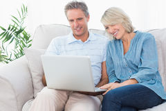 Happy couple using laptop together on the couch Royalty Free Stock Photo