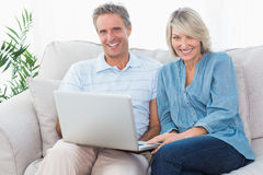 Happy couple using laptop together on the couch looking at camer Royalty Free Stock Photos