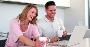 Happy couple using the laptop together and having coffee Royalty Free Stock Photography