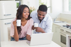 Happy couple using laptop together Stock Image