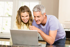 Happy couple using laptop together Stock Photo
