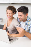 Happy couple using laptop together to shop online Stock Image