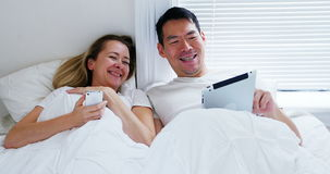 Happy couple using mobile phone digital tablet on bed. In bedroom stock video