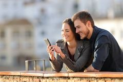 Happy couple using phone in a balcony at sunset stock photos