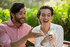 Happy couple using smart phone at park Royalty Free Stock Images