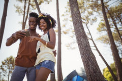Happy couple using smart phone while standing by tent Royalty Free Stock Photo