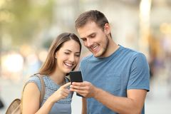 Happy couple using a smart phone on the street Royalty Free Stock Photo