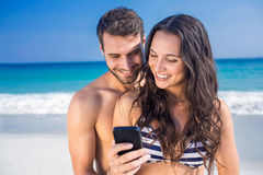 Happy couple using smartphone at the beach Royalty Free Stock Photo