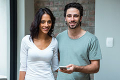 Happy couple using smartphone in living room Royalty Free Stock Photography