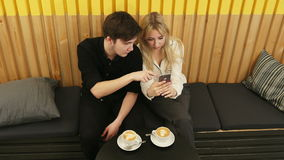 Happy couple using smartphone together and drinking coffee in cafe. Top view. Professional shot in 4K resolution. 089. You can use it e.g. in your commercial stock footage