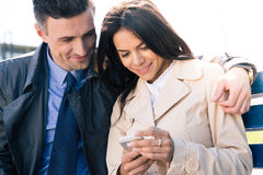 Happy couple using smartphone together Royalty Free Stock Photo