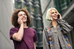 Happy couple using smartphone in urban background. Young man and woman wearing casual clothes in a London street royalty free stock photo