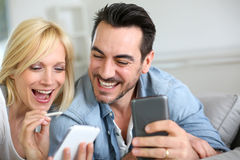 Happy couple using smartphones at home Stock Photo