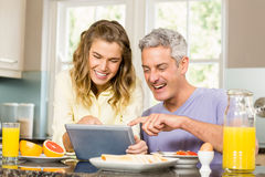 Happy couple using tablet and having breakfast Royalty Free Stock Image