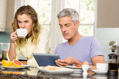 Happy couple using tablet and having breakfast Stock Images