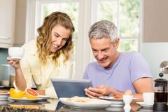 Happy couple using tablet and having breakfast Stock Image