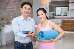 Happy couple using tablet and holding mat Stock Photo