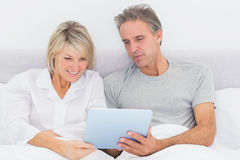 Happy couple using tablet pc in bed Royalty Free Stock Image