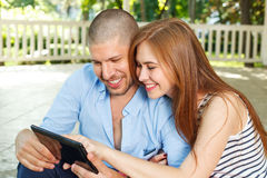 Happy couple using a tablet PC in the park Royalty Free Stock Photos