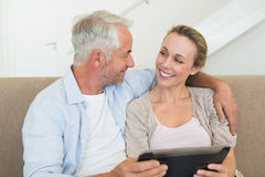 Happy couple using tablet pc together on the couch Royalty Free Stock Image