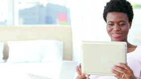 Happy couple using tablet and reading book. Portrait of a happy couple using tablet and reading book on the sofa stock video