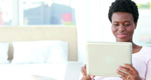 Happy couple using tablet and reading book. Portrait of a happy couple using tablet and reading book on the sofa stock video footage
