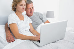 Happy couple using their laptop together in bed Royalty Free Stock Image