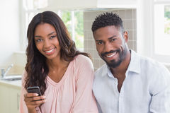Happy couple using their phones at breakfast Royalty Free Stock Image