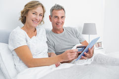 Happy couple using their tablet pc to buy online Royalty Free Stock Photography