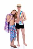 Happy couple, vacation. Attractive young couple in beach clothing, going on vacation.  Studio shot, white background, reflective surface Royalty Free Stock Photos