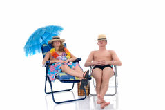 Happy couple, vacation. Attractive young couple in beach clothing, going on vacation.  Studio shot, white background, reflective surface Royalty Free Stock Image