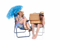 Happy couple, vacation. Attractive young couple in beach clothing, going on vacation.  Studio shot, white background, reflective surface Stock Photography