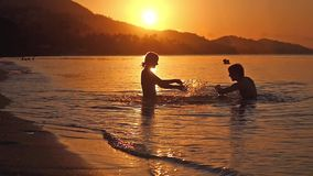 Happy couple on vacation at the beach. Sea Splashing over sunset in slow motion. 1920x1080. Happy family on vacation at the beach. Sea Splashing over sunset in stock footage