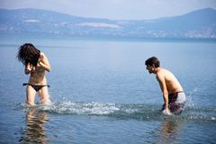 Happy couple in vacation splashing water at each other Royalty Free Stock Image