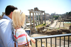 Happy couple visiting Roman Forum with tablet in hands Royalty Free Stock Photo