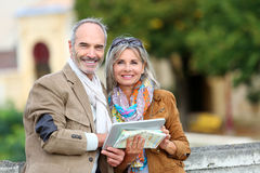Happy couple visiting town with tablet and map Royalty Free Stock Images